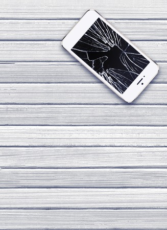 Modern mobile phone with broken screen on white wooden background photo