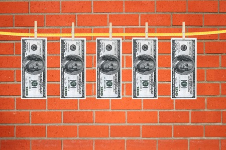 pay wall: dollars laundering and dry after wash hang on clothespins over orange brick wall
