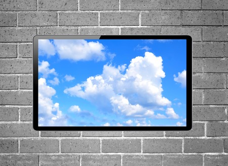 plazma: Blank screen LCD tv with blue sky hanging on a wall Stock Photo