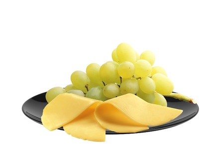 fruit plate: cheese and ripe grapes on black plate isolated on white Stock Photo