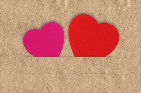 Paper hearts on brown background, close up