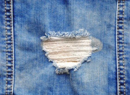 rend: Blue denim jeans in bright color tear up surface condition present the old damaging fabric damaged detail of texture background