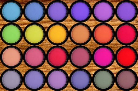 strewed: colorful eyeshadows in black boxes on the wooden background Stock Photo