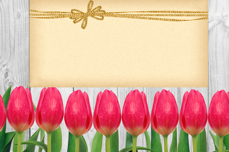 loveliness: Beautiful bright tulips and card with golden bow on wooden background