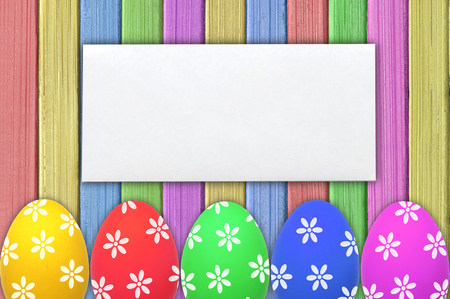 envelop: Colorful Easter eggs and white envelop on painted color wooden texture