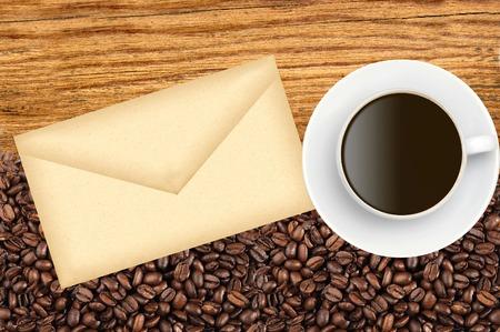 cafe colombiano: Primer plano de los granos de café tostados y envuelven y la taza de café sobre fondo de madera Foto de archivo
