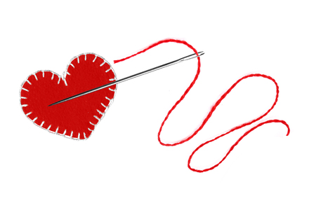 Red heart, thread and needle isolated on white