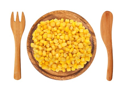 yellow corn: sweet corn grain on wooden plate, fork and knife isolated on white background