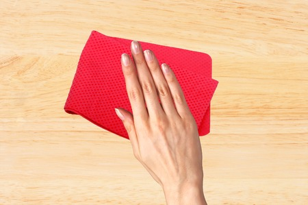 Hand wiping wooden table with red rag Stock Photo