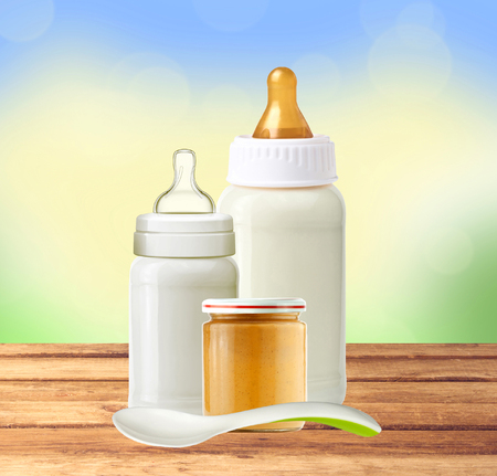 grow food: baby milk bottles, jar of baby puree and spoon on wooden table over nature background