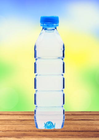 plastik: Blue bottle with water on wooden table over blurred nature background