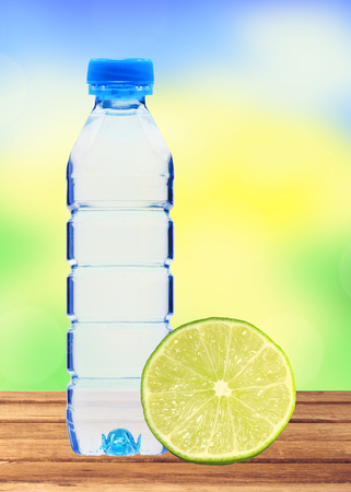 plastik: Blue bottle with water and fresh lime on wooden table over blurred nature background Stock Photo
