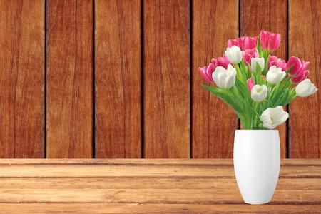 loveliness: Bouquet of pink and white tulips in vase on wooden table and wooden background