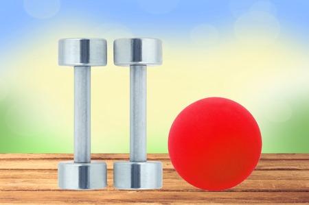 chromed: Chromed fitness dumbbells and red ball on wooden table over nature background Stock Photo