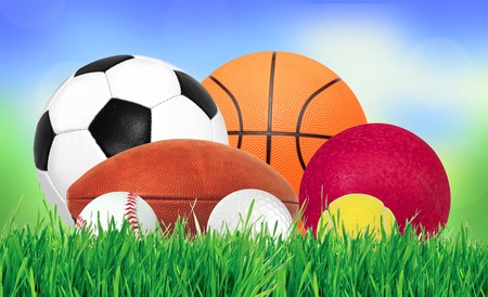 sports balls: Sports balls over green grass over nature background Stock Photo