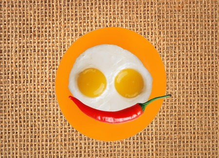 chilly: two fried eggs and red hot chilly pepper on orange plate, knife and fork on burlap Stock Photo