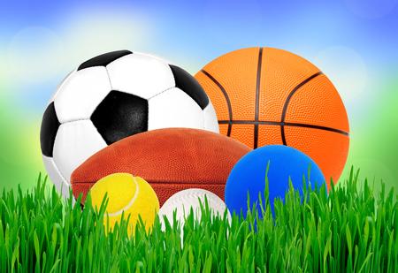 balones deportivos: Se divierte bolas en la hierba verde sobre fondo de la naturaleza borrosa