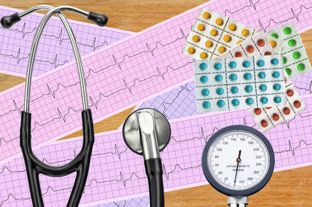 blood pressure bulb: Blood pressure meter, digital tablet, pills and stethoscope on wooden table Stock Photo