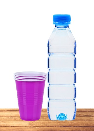 geen: Blue bottle with water and plastic cups on wooden table isolated on white Stock Photo