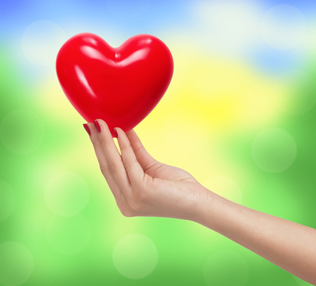 goodness: Red heart in woman hand over bright blurred nature background