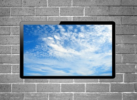 plazma: Blank screen LCD tv with blue sky screen hanging on a wall Stock Photo