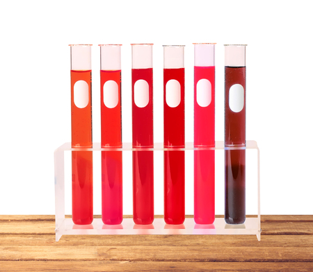 Medical test tubes with blood in holder on wooden table isolated on white background