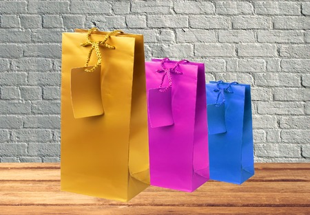 occasion: Colorful gift shopping bags on wooden table over grey brick wall