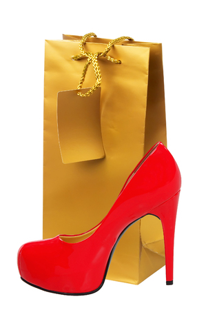 high  heeled: Golden gift shopping bag and red high heeled woman shoe isolated on white background Stock Photo