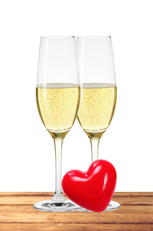 gold flute: Two glasses of champagne and red heart on table isolated on white background