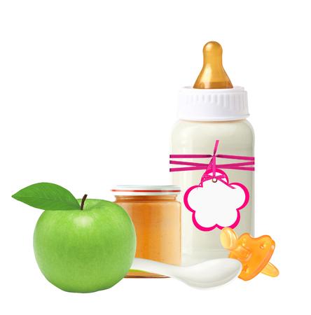 teteros: Tarro de puré de bebé, botella de leche del bebé, la manzana y el maniquí aislado en blanco Foto de archivo