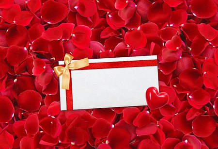 envelop: beautiful red rose petals background and envelop (letter) with red ribbon and heart Stock Photo