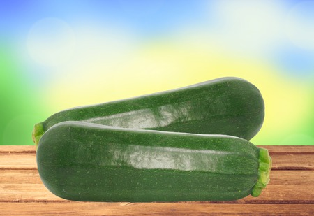 phallic: Fresh zucchini on wooden table over nature background