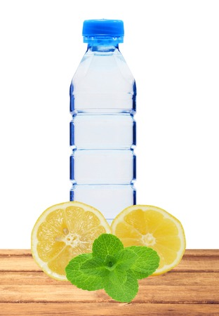 Blue bottle with water, mint and fresh yellow lemon on table isolated on white background