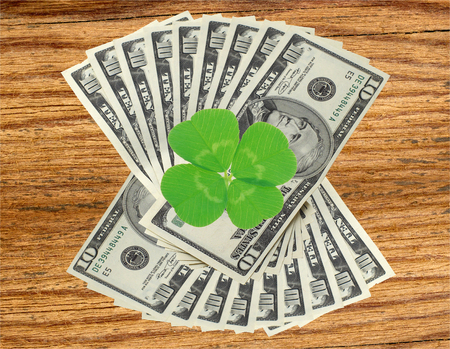 quarterfoil: Clover leaf and dollars on wooden table background