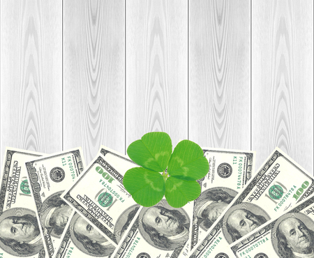 Clover leaf and dollars and white wooden table, close-up