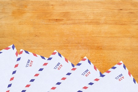 Color letters envelopes on wooden texture close-up