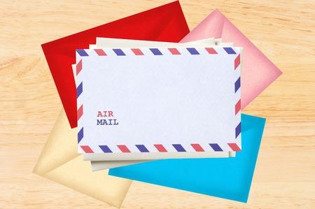 enveloped: Color letters envelopes over wooden texture