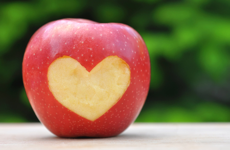 achievment: red apple with heart symbol on wooden table over nature background Stock Photo