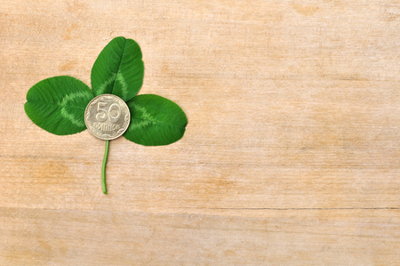 fourleafed: green clover leaf and coin on wooden board (deck) Stock Photo