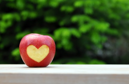 achievment: Red Apple With Heart Symbol On Wood Table Over Nature Background