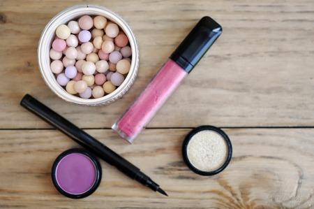 lipgloss: Makeup Set With Powder Ball, EyeShadows, Liner And Lipgloss On Wood Table