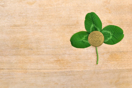 green clover leaf and coin on wooden board (deck) Stock Photo