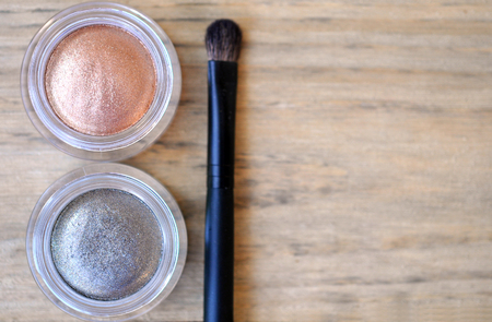 shimmer: Two shimmer eyeshadow glass boxes and brush on wood table