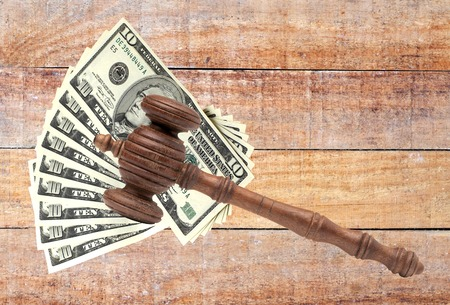 antitrust: Judges or Auctioneers Gavel Or Hammer And Big Money Stack On Wooden Bench Isolated On White Background. Concept For Financial Crime, Close Up Stock Photo