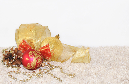 Gold and red Christmas balls, pine cone, ribbon decorations on light background