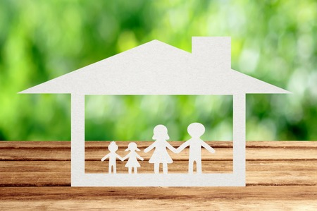 man made structure: Paper family on wooden table with garden bokeh outdoor theme background