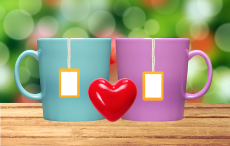 Two cups and tea bags with orange label on table over christmas lights background Stock Photo
