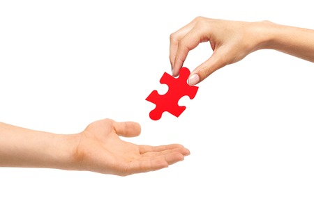 Woman hand give red puzzle to man isolated on white background