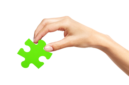 Green puzzle with woman hand isolated on white background Stock Photo