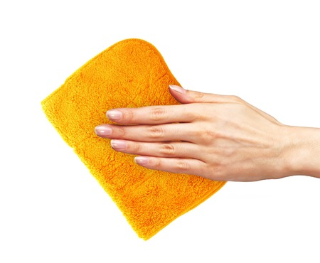 Hand wiping surface with orange rag isolated on white